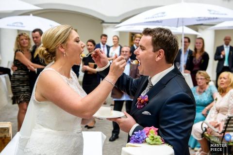Le photographe de mariage de Munich a capturé cette image d'une mariée et du marié se nourrissant le gâteau lors d'une réception en plein air