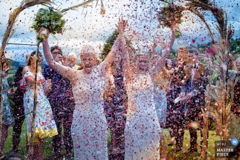 This photograph of two brides being showered in pink confetti was captured by a Bristol wedding photographer