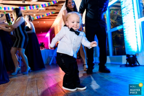 Austin wedding photographer captured this image of a toddler wearing a black bow tie showing off his dance moves on the dance floor