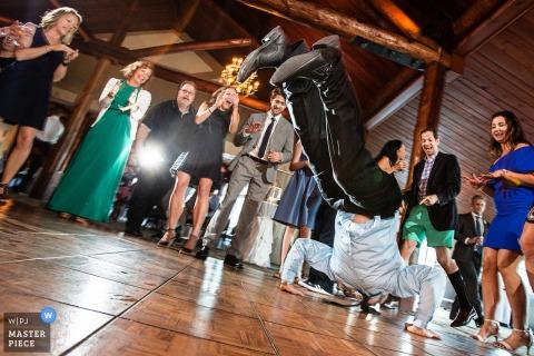 New-Jersey Hochzeitsfotograf nahm diese Fotografie eines Hochzeitsgastes gefangen, der seine Tanzbewegungen auf dem Türboden in einem Blockhaus vorführt