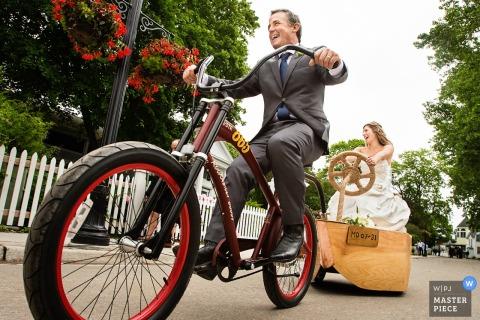 Der Hochzeitsfotograf aus New Jersey hielt den Bräutigam fest, der seine Braut nach ihrer Zeremonie glücklich in einem Karren hinter seinem Fahrrad zog