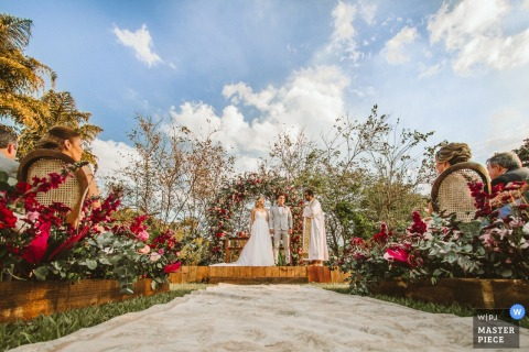 Minas Gerais wedding photographer captured this beautiful outdoor ceremony from the middle of the red flower adorned aisle while the bride and groom stand in front of a greenery adorned arch