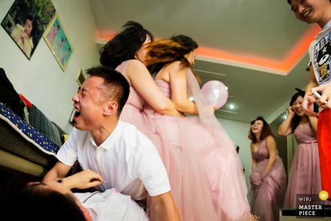 This funny image of the groom laughing as he and his bridal party pile on the floor was captured by a ChongQing wedding photographer