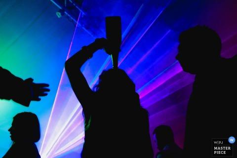 Der Londoner Hochzeitsfotograf hat die Silhouette eines Hochzeitsgastes festgehalten, der direkt aus der Flasche trinkt, während blaue und lila Lichter hinter ihnen leuchten