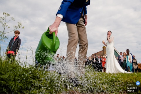 Noord-huwelijksfotograaf heeft deze foto van een bruidegom gemaakt die het gras met een gieter water geeft terwijl de bruid in de buurt kijkt