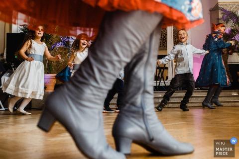 De trouwfotograaf van Sint-Petersburg heeft dit close-up van grijze laarzen op de dansvloer gevangen terwijl een rij kinderen achterom danst en lacht