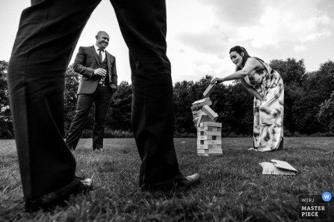 Hertfordshire wedding photographer captured this wedding guests game of lawn Jenga right when the tower tumbled to the grass