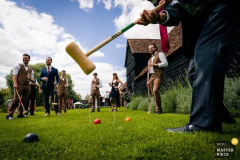 Hertfordshire wedding photographer captured this ground level view of the groomsmen playing croquet on a sunny day