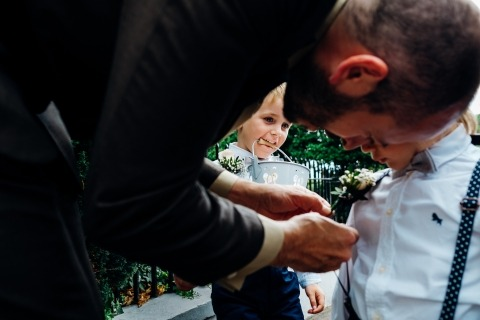 UK Reportage Wedding Photographer Marianne Chua of London, captured this ring bearer getting his flower pinned on.