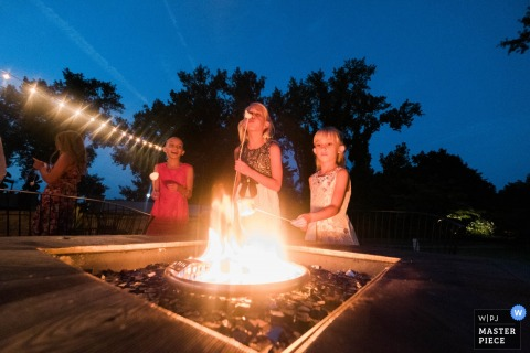 Connectcuit wedding photographer captured this photo of young wedding guests roasting marshmallows under a night sky