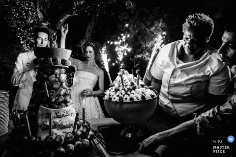 De bruid en bruidegom vieren hun huwelijk met vlammende desserts terwijl een huwelijksfotograaf uit Montpellier het moment vastlegt in deze zwart-witfoto