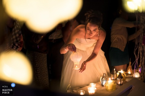 The bride tentatively holds a miniature paper lantern as she gets ready to release it as a Nouvelle-Aquitaine wedding photographer captured the moment from a distance