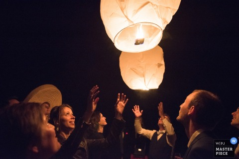 Nouvelle-Aquitaine wedding photographer captured the awe on the wedding guests faces as they released their flaming lanterns into the dark night sky