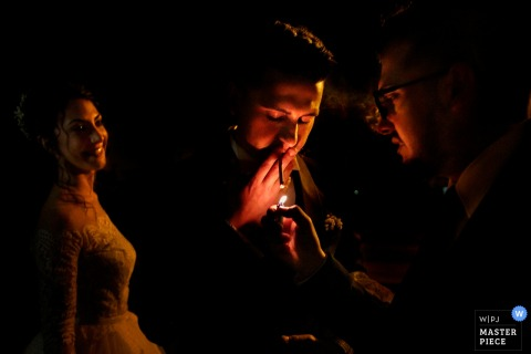 Reggio Calabria wedding photographer captured this photo of a wedding guest helping the groom light his cigarette as the bride smiles nearby