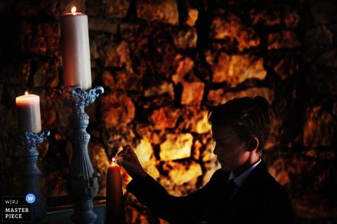De huwelijksfotograaf van Lyon ving deze foto van een jonge jongen die een kleine kaars voor een steenmuur aansteken