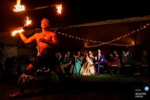 Le photographe de mariage de Los Angeles a capturé cette photo d'un artiste de performance de feu se produisant lors d'une réception de mariage en plein air, tandis que les invités du mariage regardaient sous des lumières scintillantes