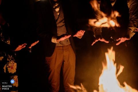 El fotógrafo de bodas de Roma capturó esta imagen detallada de los invitados a la boda calentándose las manos junto a un fuego rugiente