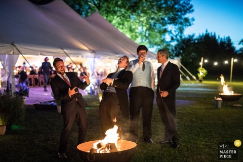 Der Londoner Hochzeitsfotograf hat dieses Foto von vier Freunden aufgenommen, die am Feuer lachen und trinken, während ein großes Hochzeitszelt hinter ihnen aufgebaut ist