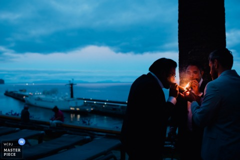 Porto wedding photographer captured this photo of the groom and groomsmen enjoying cigars outside at dusk