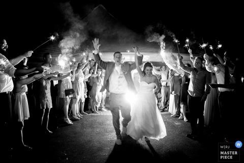 Fotograf ślubny Lake Tahoe uchwycił to czarno-białe zdjęcie młodej pary, opuszczając przyjęcie weselne pod tunelem zimnych ognisk w rękach gości weselnych