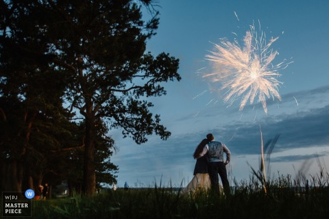 Sint-Petersburg huwelijksfotograaf heeft deze foto van een bruid en bruidegom omarmd in het midden van een grasveld bij zonsondergang terwijl vuurwerk hierboven explodeert