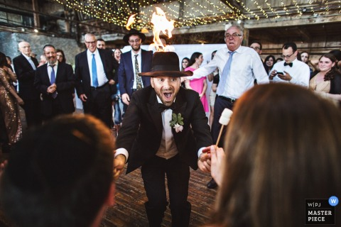 Brooklyn wedding photographer captured this photo of a fire performer handing out marshmallows for the wedding guests to roast on a flame coming from his hat