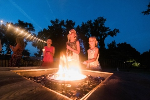 Connecticut-Hochzeits-Fotograf Eric Brushett macht Fotos von den Kindern, die eine Feuergrube im Freien an einer Hochzeitsempfang-Partei genießen.