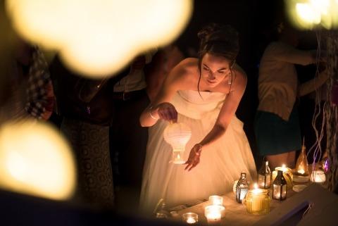Dokumentarischer Hochzeits-Fotograf Valerie Teppe von Frankreich nahm die Braut gefangen, die Kerzenlaternen an ihrer Empfangsabendessenparty beleuchtet.