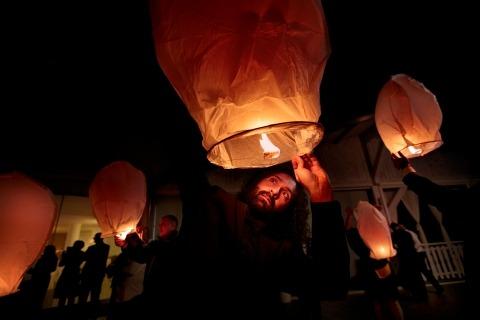 Wedding Photojournalism von Danilo Coluccio aus Reggio Calabria, Italien, zeigt diese Feuerlaternenballons, die an der Rezeption angezündet werden.