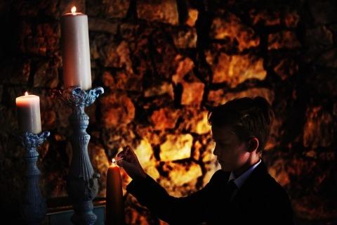 Dokumentarischer Hochzeits-Fotograf Franck Boutonnet von Frankreich machte dieses Bild eines Jungen, der Kerzen an einer Hochzeitszeremonie beleuchtet.