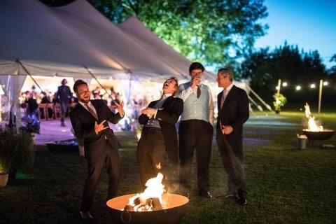 Wedding Photojournalism von Harry Richards aus London zeigt diesen Jungs die Feuerstelle vor einem Zeltempfang.