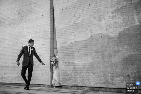 Madison wedding photographer captured this photo of the groom reaching for his bride who is seemingly appearing out of a large crack in the wall
