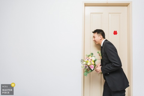 Singapore wedding photographer captured this photo of a groom talking excitedly through the door to his bride before the wedding