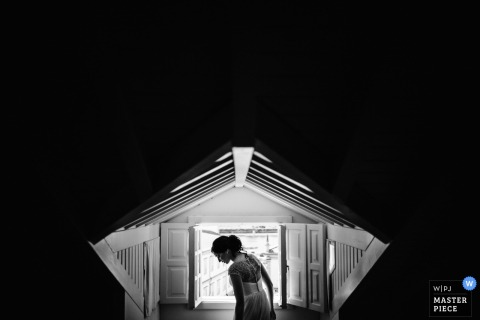 Porto wedding photographer captured this black and white photo of a bride standing in front of a brightly lit open window while the space behind is completely dark
