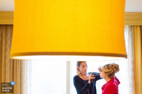 New Jersey wedding photographer captured this image of bride getting her make-up finished in front of a big window
