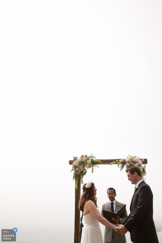 San Fransisco wedding photographer capture this image of a wedding ceremony being held under an flower adorned wooden arch under an overcast sky