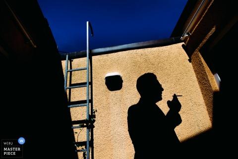 Der deutsche Hochzeitsfotograf schuf dieses Foto des Schattens eines Hochzeitsgastes, der gegen eine Wand geworfen wurde, während er rauchend draußen stand