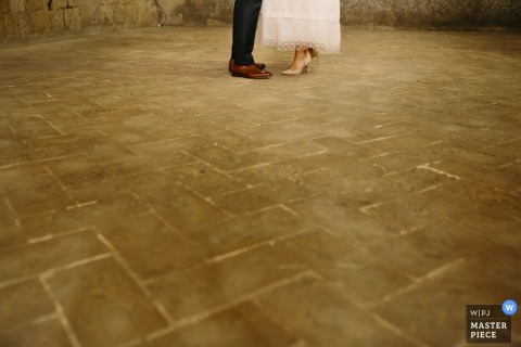 Arezzo wedding photographer captured this detail image of the bride and grooms shoes as they stand toe to toe on a stone floor