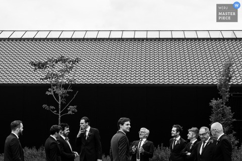 Antwerpen wedding photographer captured this black and white photo of the groom and groomsmen waiting patiently for the ceremony to start outside of a large building with a tiled roof