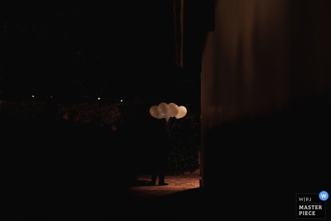 Madrid wedding photographer captured this minimalist image of a single wedding guest holding white balloons in the dark