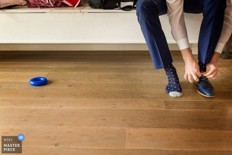 Noord Holland wedding photographer captured this detail shot of a groom putting on his dress shoes while kids toys lay on the floor beside him
