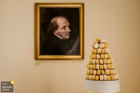 Kent wedding photographer captured this detail image of a painted portrait of an old man looking disparagingly at a cake comprised of macaroons