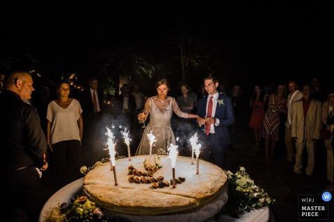 Der französische Hochzeitsfotograf hat diese Braut und den Bräutigam mit großen Feuerwerkskerzen auf ihrer riesigen runden Hochzeitstorte festgehalten