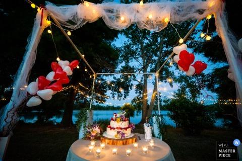 Un fotógrafo de bodas de Brescia capturó este detalle de un pastel sentado en una mesa frente a un lago con globos en forma de corazón en el fondo.