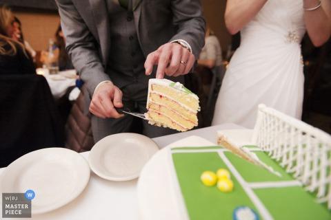 Questo colpo di dettaglio di una fetta di torta tagliata da una torta nuziale a tema tennis è stato catturato da un fotografo di matrimoni di Boston