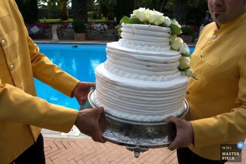 El fotógrafo de bodas de Cantania capturó esta foto de un simple pastel de bodas blanco que se lleva en una bandeja de plata.
