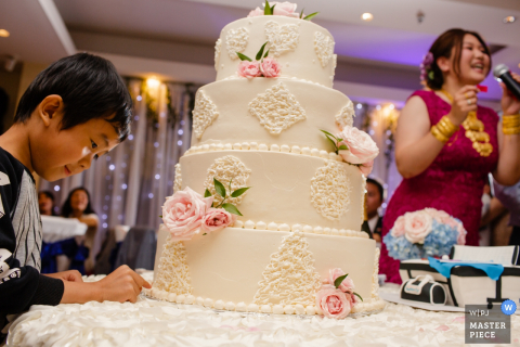 San Jose wedding photographer caught a young wedding guest in the act of stealing some frosting of a pink rose adorned wedding cake