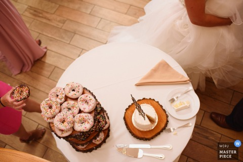 El fotógrafo de bodas de Outerbanks capturó esta foto desde arriba de una mesa de postres única con una tarta de donuts y una pequeña tarta blanca que descansa sobre un trozo circular de madera