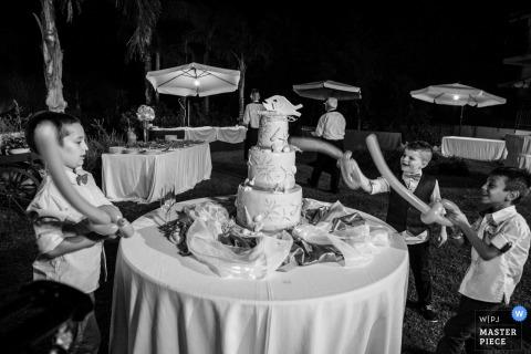 To czarno-białe zdjęcie małych chłopców udających, że kroi ciasto balonowymi mieczami, zostało uchwycone przez fotografa ślubnego z Sycylii