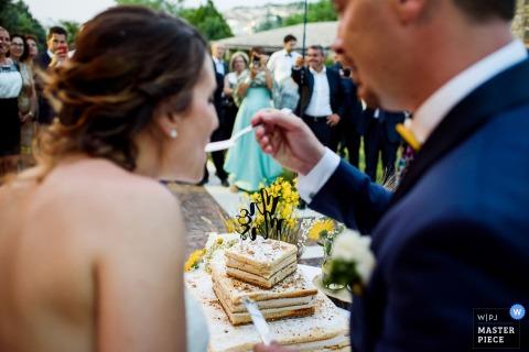 Apulien-Hochzeitsfotograf nahm dieses Bild eines Bräutigams gefangen, der seiner Braut den ersten Bissen ihrer quadratischen Hochzeitstorte einzieht